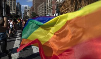 In this June 30, 2019, file photo parade-goers carrying rainbow flags walk down a street during the LBGTQ Pride march in New York, to celebrate five decades of LGBTQ pride, marking the 50th anniversary of the police raid that sparked the modern-day gay rights movement. (AP Photo/Wong Maye-E) ** FILE **