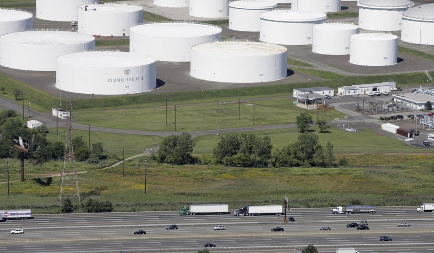 """In this Sept. 8, 2008 file photo traffic on I-95 passes oil storage tanks owned by the Colonial Pipeline Company in Linden, N.J. A major pipeline that transports fuels along the East Coast says it had to stop operations because it was the victim of a cyberattack. Colonial Pipeline said in a statement late Friday that it """"took certain systems offline to contain the threat, which has temporarily halted all pipeline operations, and affected some of our IT systems."""" (AP Photo/Mark Lennihan, File)  **FILE**"""