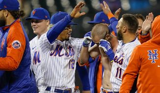 New York Mets' Francisco Lindor (12) celebrates with Patrick Mazeika, center right, who had his jersey removed by his teammates as they celebrate after Pete Alonso scored the winning run against the Arizona Diamondbacks on a grounder by Mazeika in the 10th inning of a baseball game Friday, May 7, 2021, in New York. (AP Photo/John Minchillo)