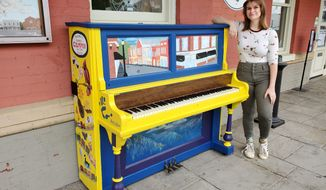 Culpeper artist Jordan Wilson poses with the piano whose artwork she designed and painted, now part of the Culpeper Keys program at the town Visitors Center,  on Monday, May 3, 2021 in Culpeper, Va. (Emily Jennings/The Star-Exponent via AP)