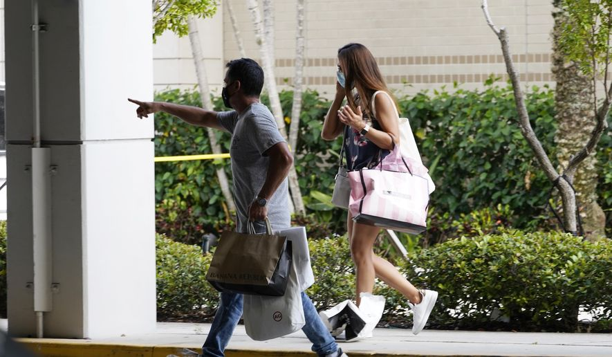 Shoppers walk toward a garage after leaving the Aventura Mall where a shooting left three people injured and several suspects in custody, Saturday, May 8, 2021, in Aventura, Fla. Aventura Police said two groups of people had begun fighting in the mall when shots rang out. (AP Photo/Marta Lavandier)