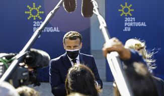 French President Emmanuel Macron speaks with the media as he arrives for an EU summit at the Crystal Palace in Porto, Portugal, Saturday, May 8, 2021. On Saturday, EU leaders hold an online summit with India's Prime Minister Narendra Modi, covering trade, climate change and help with India's COVID-19 surge. (Violeta Santos Moura, Pool via AP)