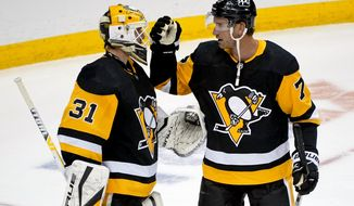 Pittsburgh Penguins goaltender Maxime Lagace (31) celebrates his first career shutout with Jeff Carter after an NHL hockey game against the Buffalo Sabres in Pittsburgh, Saturday, May 8, 2021. The Penguins won 1-0. (AP Photo/Gene J. Puskar)
