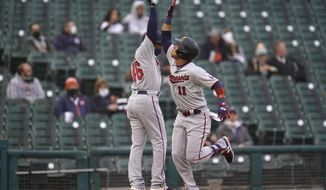 Minnesota Twins' Jorge Polanco (11) celebrates his solo home run with third base coach Tony Diaz (46) against the Detroit Tigers in the second inning of a baseball game in Detroit, Friday, May 7, 2021. (AP Photo/Paul Sancya)