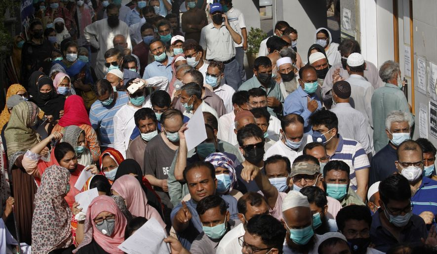 People stand in queues while they wait their turn to receive the first shot of the Sinopharm COVID-19 vaccine at a vaccination center in Karachi, Pakistan, Saturday, May 8, 2021. (AP Photo/Fareed Khan)
