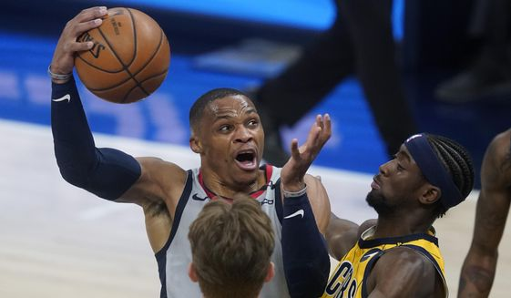Washington Wizards' Russell Westbrook goes to the basket against Indiana Pacers' Caris LeVert (22) during the first half of an NBA basketball game Saturday, May 8, 2021, in Indianapolis. (AP Photo/Darron Cummings)