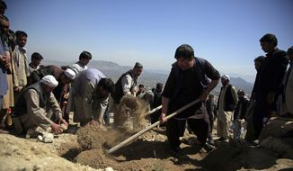 Afghan men bury a victim of deadly bombings on Saturday near a school, west of Kabul, Afghanistan, Sunday, May 9, 2021. The Interior Ministry said Sunday the death toll in the horrific bombing at the entrance to a girls' school in the Afghan capital has soared to some 50 people, many of them pupils between 11 and 15 years old, and the number of wounded in Saturday's attack has also climbed to more than 100. (AP Photo/Mariam Zuhaib)