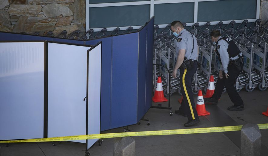 Royal Canadian Mounted Police officers search around rows of luggage carts as screens block off an area of the sidewalk after a shooting outside the international departures terminal at Vancouver International Airport, in Richmond, British Columbia, Sunday, May 9, 2021. (Darryl Dyck/The Canadian Press via AP)