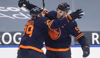 Edmonton Oilers' Connor McDavid (97) and Leon Draisaitl (29) celebrates after McDavid's 100th point of the season, during the second period of an NHL hockey game against the Vancouver Canucks on Saturday, May 8, 2021, in Edmonton, Alberta. (Jason Franson/The Canadian Press via AP)
