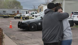 Family and friends of the victims who died in a shooting, comfort each down the street from the scene in Colorado Springs, Colo., on Sunday, May 9, 2021. The suspected shooter was the boyfriend of a female victim at the party attended by friends, family and children. He walked inside and opened fire before shooting himself, police said. Children at the attack weren't hurt and were placed with relatives. (Jerilee Bennett/The Gazette via AP)