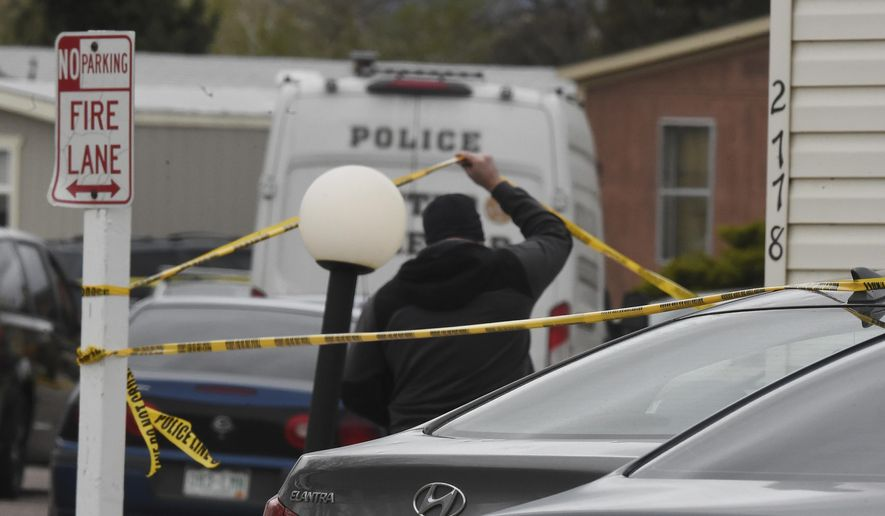 A Colorado Springs Police Department officer lifts up crime tape at the scene where multiple people were shot and killed early Sunday, May 9, 2021, in Colorado Springs, Colo. The suspected shooter was the boyfriend of a female victim at the party attended by friends, family and children. He walked inside and opened fire before shooting himself, police said. Children at the attack weren't hurt and were placed with relatives. (Jerilee Bennett/The Gazette via AP)