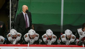 Arizona Coyotes head coach Rick Tocchet, standing, watches the game during the second period of an NHL hockey game Wednesday, April 14, 2021, in St. Paul, Minn. The Wild won 5-2. (AP Photo/Craig Lassig)