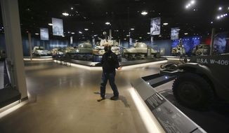 Dan Starks stands in one of the large galleries of the National Museum of Military Vehicles Wednesday, April 14, 2021, in Dubois, Wyo., depicting the progress of American military vehicles throughout World War II and beyond. Starks built the new museum for his collection of military equipment. The Casper Star-Tribune reports Starks bought a Sherman tank to restore a decade ago and after that built up a collection of tanks, jeeps, trucks, motorcycles, guns, artillery and even aquatic landing craft. (Cayla Nimmo/The Casper Star-Tribune via AP)