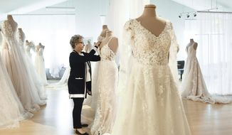 """""""We're used to surviving, and we're used to doing what it takes,"""" Sue Rosenberger of Fantastic Finds says Thursday, April 22, 2021, about her shop in Lansing Township, Mich., that specializes in wedding gowns, dresses, suits, and tuxedo rental. Fantastic Finds currently allows couples to bring along iPads to fittings so they can video chat out-of-state or at-risk family members.  (Matthew Dae Smith/Lansing State Journal via AP)"""