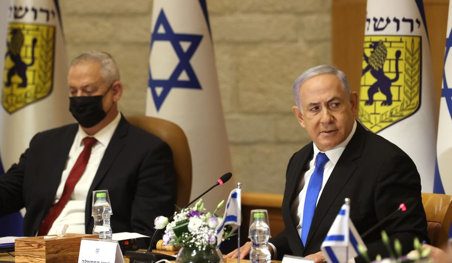 Israeli Prime Minister Benjamin Netanyahu, right, and Minister of Defense Benny Gantz  attend a special cabinet meeting on the occasion of Jerusalem Day, at the Jerusalem Municipality building, in Jerusalem, Sunday, May 9, 2021. (Amit Shabi/Pool Photo via AP)