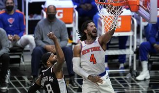 New York Knicks guard Derrick Rose (4) scores past Los Angeles Clippers forward Marcus Morris Sr. (8) during the first half of an NBA basketball game Sunday, May 9, 2021, in Los Angeles. (AP Photo/Marcio Jose Sanchez)