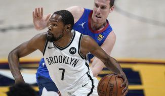 Brooklyn Nets forward Kevin Durant drives against Denver Nuggets forward Vlatko Cancar during the second half of an NBA basketball game Saturday, May 8, 2021, in Denver. (AP Photo/David Zalubowski)