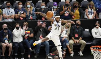 Utah Jazz forward Royce O'Neale (23) saves the ball as fans sitting courtside watch during the first half of the team's NBA basketball game against the Houston Rockets on Saturday, May 8, 2021, in Salt Lake City. (AP Photo/Rick Bowmer)