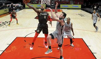 Portland Trail Blazers guard Damian Lillard, left drives to the basket on San Antonio Spurs forward Drew Eubanks, right, during the second half of an NBA basketball game in Portland, Ore., Saturday, May 8, 2021. The Blazers won 124-102. (AP Photo/Steve Dykes)