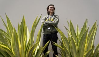 Lucius Giannini stands for a portrait Thursday, April 15, 2021, in San Diego. Giannini graduated from the University of California at San Diego at the end of last summer with a degree in political science. He had hoped to find work with the Peace Corps, or maybe teaching English overseas. But the Peace Corps was bringing all its volunteers home, and no one was hiring for overseas teaching. (AP Photo/Gregory Bull)
