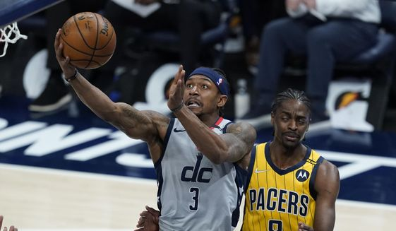 Washington Wizards' Bradley Beal (3) is fouled by Indiana Pacers' Justin Holiday (8) as he goes up for a shot during the first half of an NBA basketball game, Saturday, May 8, 2021, in Indianapolis. (AP Photo/Darron Cummings) **FILE**