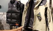 A worker shows a jacket at The North Face store in New York. (AP Photo/Ted Shaffrey)