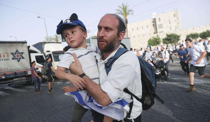Israelis run to shelters as air attack sirens goes off during a Jerusalem Day march, in Jerusalem, Monday, May 10, 2021. Explosions have been heard in Jerusalem after air raid sirens sounded. The sirens came Monday, shortly after the Hamas militant group in Gaza had set a deadline for Israel to remove its security forces from the Al-Aqsa Mosque compound. (AP Photo/Ariel Schalit)