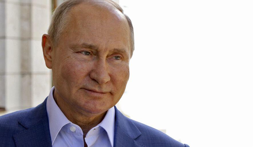 Russian President Vladimir Putin smiles as he meets with IIHF President Rene Fasel in the Bocharov Ruchei residence in the Black Sea resort of Sochi, Russia, Monday, May 10, 2021. (Mikhail Klimentyev, Sputnik, Kremlin Pool Photo via AP)