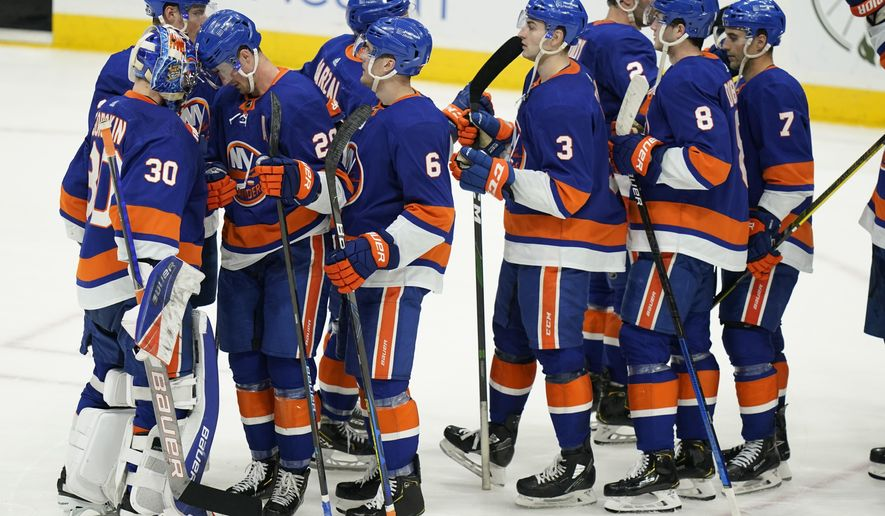 New York Islanders goaltender Ilya Sorokin (30) and Brock Nelson (29) celebrate with teammates after an NHL hockey game against the New Jersey Devils Saturday, May 8, 2021, in Uniondale, N.Y. The Islanders won 5-1. (AP Photo/Frank Franklin II)