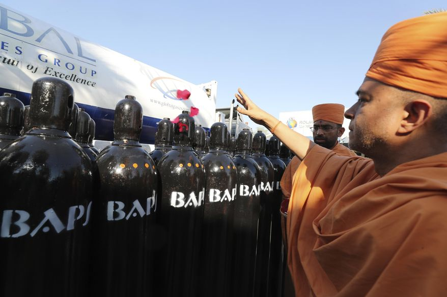 Brahmavihari Swami, the head of BAPS Shri Swaminarayan Mandir, the main Hindu temple in Abu Dhabi, throws rose petals during a blessing ceremony before shipping hundreds of liquid oxygen cylinders and massive containers of compressed oxygen to India, in Jebel Ali Free Zone, Dubai, United Arab Emirates, Monday, May 10, 2021. The organizers, Indian owners of Global Gases Group, a Dubai helium factory, shifted production to oxygen when the latest surge in virus cases hit India. (AP Photo/Kamran Jebreili)