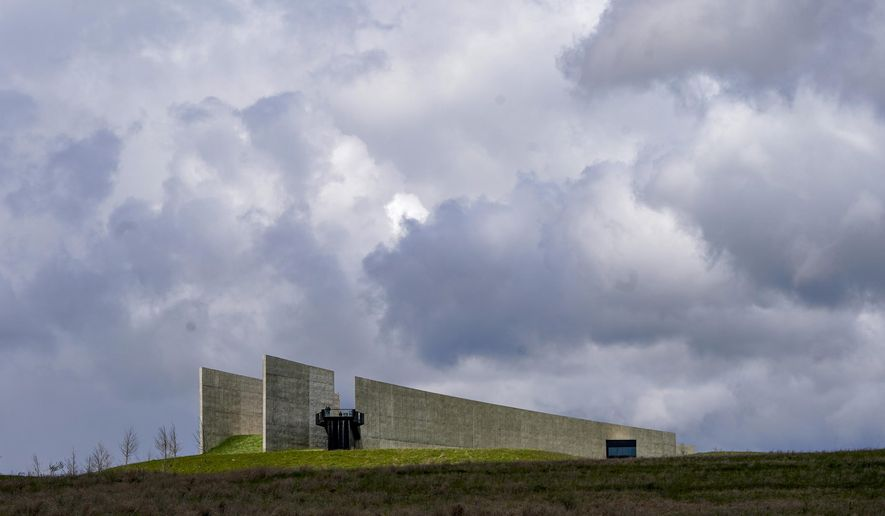 Visitors look from the observation platform at the Flight 93 National Memorial under a cloudy sky on Saturday, May 8, 2021, in Shanksville, Pa. (AP Photo/Keith Srakocic)
