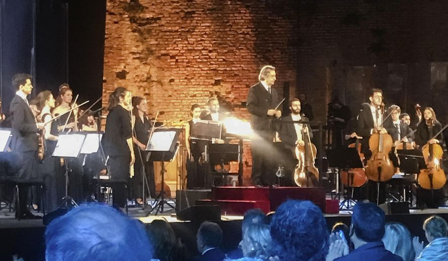 FILE - In this June 21, 2020 file photo, Italian Maestro Riccardo Muti, top center, prepares to direct a concert at the Ravenna Festival, in Ravenna, Italy. With a purposeful nod and flick of his baton, the 79-year-old conductor on Sunday, May 9, 2021, ended what has been an unexpectedly long silence in Italian theaters, enrapturing a socially distanced and masked audience with the Vienna Philharmonic Orchestra's first live performances since fall, two evening concerts of Mendelssohn, Schumann and Brahms, in his adopted hometown of Ravenna. (AP Photo/Colleen Barry, file)