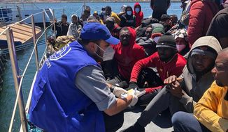 Aid workers for the International Organization for Migration provide assistance to migrants who were intercepted off the Libyan coast, at the Abu Sitta disembarkation point in Tripoli, Sunday, May 9, 2021. The organization said that more than 700 migrants were intercepted Sunday by the Libyan coast guard off the coast of the North African country, and at least 5 people had drowned when a boat carrying at least 45 migrants capsized. (International Organization for Migration via AP)