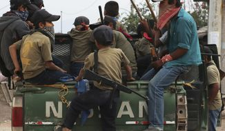 In this file photo, children, some carrying real weapons and others with fake ones, patrol their community aboard a pick-up truck as part of a display by community leaders to call the government's attention to their town's plight in Ayahualtempa, Guerrero state, Mexico, Wednesday, April 28, 2021.  (AP Photo/Marco Ugarte)  **FILE**