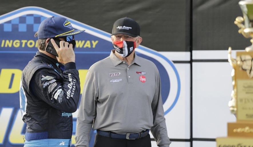 Martin Truex Jr. talks on a cell phone as team owner Joe Gibbs stands nearby after Truex won the NASCAR Cup Series auto race at Darlington Raceway, Sunday, May 9, 2021, in Darlington, S.C. (AP Photo/Terry Renna) **FILE**