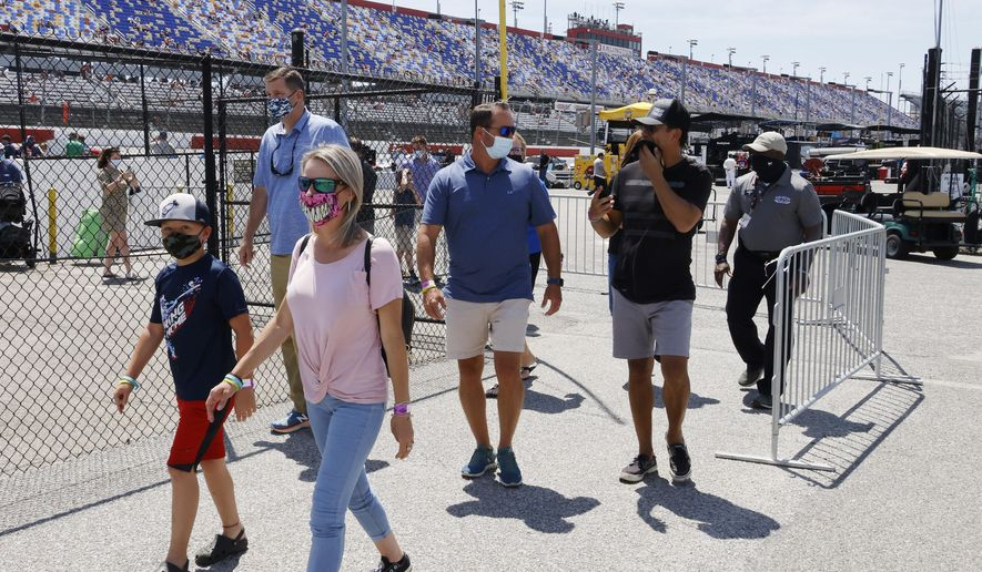 Fans walk through the garage area before a NASCAR Cup Series auto race at Darlington Raceway, Sunday, May 9, 2021, in Darlington, S.C. It is the first time this year that fans are allowed back in the garage area. (AP Photo/Terry Renna) **FILE**