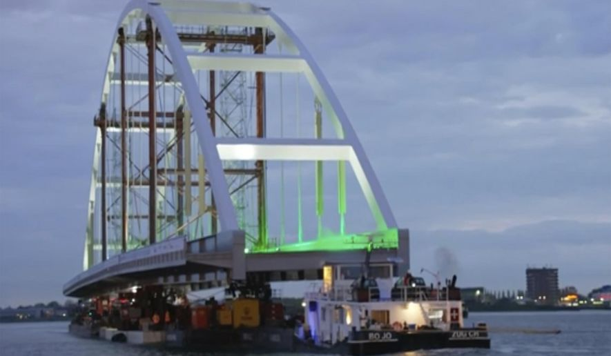 In this image taken from video released by Netherlands Department of Waterways and Public Works, showing a 200-metre (656-feet) long bridge taking a slow cruise through the heart of Rotterdam as it heads towards its new temporary home near the city's busy port area early Monday May 10, 2021 in Rotterdam.  Tug boats moved the 20 metres (65 feet) wide and with a 40 metre (131 feet) high arch, Suurhoff Bridge early on Monday supported on pontoons under a series of other bridges on the Maas River that bisects the Dutch city. (RIJKSWATERSTAAT Department of Waterways and Public Works via AP)