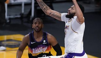 Los Angeles Lakers forward Anthony Davis, right, reaches for a rebound over Phoenix Suns guard Chris Paul during the first half of an NBA basketball game Sunday, May 9, 2021, in Los Angeles. (AP Photo/Marcio Jose Sanchez)