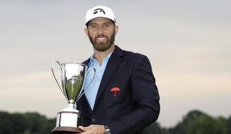 In this June 28, 2020, file photo, Dustin Johnson poses with the trophy after winning the Travelers Championship golf tournament at TPC River Highlands, Sunday, in Cromwell, Conn. Johnson says it was surreal sinking the final putt to win last year's Travelers Championship with fewer than 40 spectators politely clapping instead of the thousands that usually fill the bowl surrounding the 18th green at TPC River Highlands. (AP Photo/Frank Franklin II, File) **FILE**