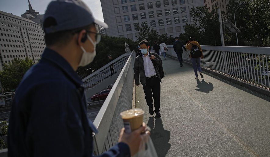 People wearing face masks to help curb the spread of the coronavirus walk on a pedestrian overhead bridge as they heading to work in Beijing, Monday, May 10, 2021. (AP Photo/Andy Wong)