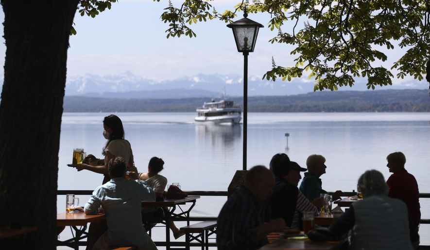 People enjoy the sunny weather and drink beer on the re-opening day of beer gardens, following the lifting of measures to avoid the spread of the corona virus, at lake 'Ammersee' in front of the alps in Inning, Germany, Monday, May 10, 2021. (AP Photo/Matthias Schrader)