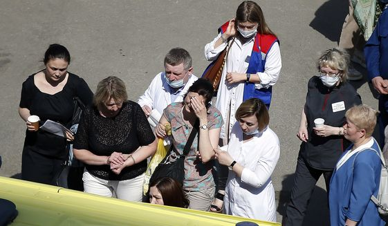 Medics and friends help a woman board an ambulance at a school after a shooting in Kazan, Russia, Tuesday, May 11, 2021. Russian media report that several people have been killed and four wounded in a school shooting in the city of Kazan. Russia's state RIA Novosti news agency reported the shooting took place Tuesday morning, citing emergency services. (AP Photo/Roman Kruchinin)