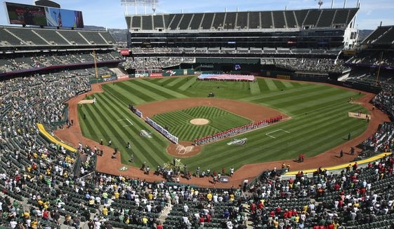 The Los Angeles Angels and Oakland Athletics stand for the national anthem at the Oakland Coliseum prior to an opening day baseball game in Oakland, Calif., in this Thursday, March 29, 2018, file photo.Major League Baseball instructed the Athletics to explore relocation options as the team tries to secure a new ballpark it hopes will keep the club in Oakland in the long term. MLB released a statement Tuesday, May 11, 2021, expressing its longtime concern that the current Coliseum site is not a viable option for the future vision of baseball. (AP Photo/Ben Margot, File) **FILE**