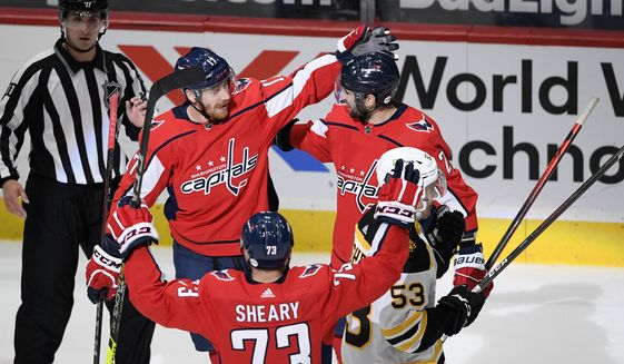 Washington Capitals left wing Michael Raffl (17) celebrates his goal with left wing Conor Sheary (73) and defenseman Justin Schultz (2) during the third period of an NHL hockey game as Boston Bruins center Cameron Hughes (53) skates away , Tuesday, May 11, 2021, in Washington. The Capitals won 2-1. (AP Photo/Nick Wass)