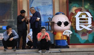 Residents smoke along the popular Wangfujing shopping district in Beijing Tuesday, May 11, 2021. The number of working-age people in China fell over the past decade as its aging population barely grew, a census showed Tuesday, adding to economic challenges for Chinese leaders who have ambitious strategic goals. (AP Photo/Ng Han Guan)