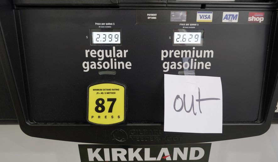 """A note posted at a gas pump indicates the pump is out of premium gasoline at a Costco Warehouse fuel station, Tuesday, May 11, 2021, in Ridgeland, Miss. State officials warn that any shortages seen at individual gas stations are a result of people """"panic buying,"""" and not the Colonial Pipeline shutdown itself. They call on residents to limit unnecessary travel and to only buy as much gasoline as they need. (AP Photo/Rogelio V. Solis)"""