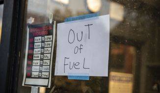"""A sign reading """"Out of Fuel"""" is taped to the window at an Exxon Gas Station on Boonsboro Road in Lynchburg, Va., Tuesday, May 11, 2021. More than 1,000 gas stations in the Southeast reported running out of fuel, primarily because of what analysts say is unwarranted panic-buying among drivers, as the shutdown of a major pipeline by hackers entered its fifth day. In response, Virginia Gov. Ralph Northam declared a state of emergency. (Kendall Warner/The News & Advance via AP)"""