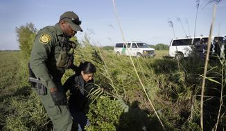 In this Aug. 11, 2017, file photo, a U.S. Customs and Border Patrol agent escorts an immigrant suspected of crossing into the United States illegally along the Rio Grande near Granjeno, Texas. (AP Photo/Eric Gay, File)