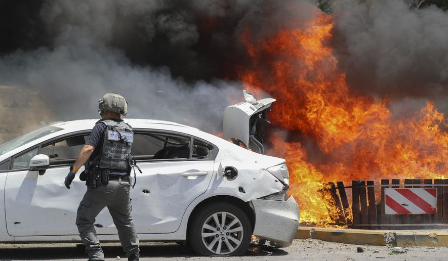 Cars burn after being hit by a missile fired from Gaza Strip, in the southern Israeli town of Ashkelon, Tuesday, May 11, 2021. (AP Photo/Ariel Schalit)