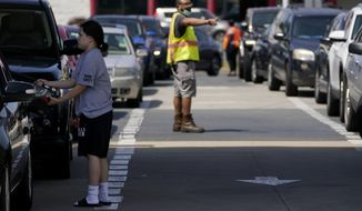 A customer pumps gas at Costco, as a worker directs traffic, on Tuesday, May 11, 2021, in Charlotte, N.C. Colonial Pipeline, which delivers about 45% of the fuel consumed on the East Coast, halted operations last week after revealing a cyberattack that it said had affected some of its systems. (AP Photo/Chris Carlson)
